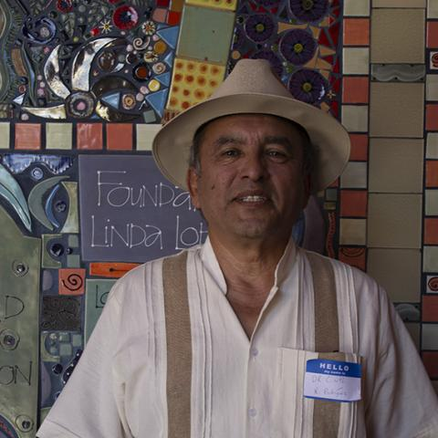Roberto standing in front of colorful tile with a straw hat on